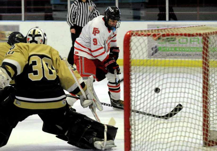 Fairfield Prep's A.J. Unker flicks the puck past Notre Dame of Fairfield's goalie Scott Kline for a point, during boys hockey action in Bridgeport, Conn. on Saturday February 11, 2012. Unker was assisted by teammate #8 David White. Photo: Christian Abraham / Connecticut Post