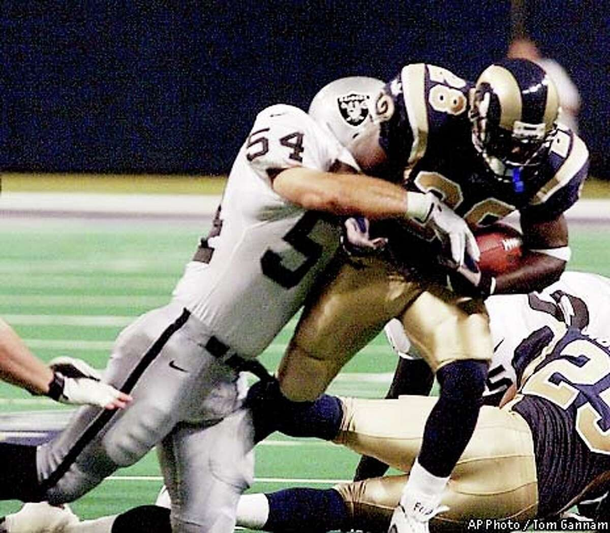 St. Louis Rams Marshall Faulk tried to break the tackle of Oakland Raiders Greg Biekert (54) in the first quarter of a preseason game Saturday, August 5, 2000, in St. Louis. Biekert has led the Raiders in tackles the past two years and four of the past six seasons. Associated Press photo by Tom Gannam