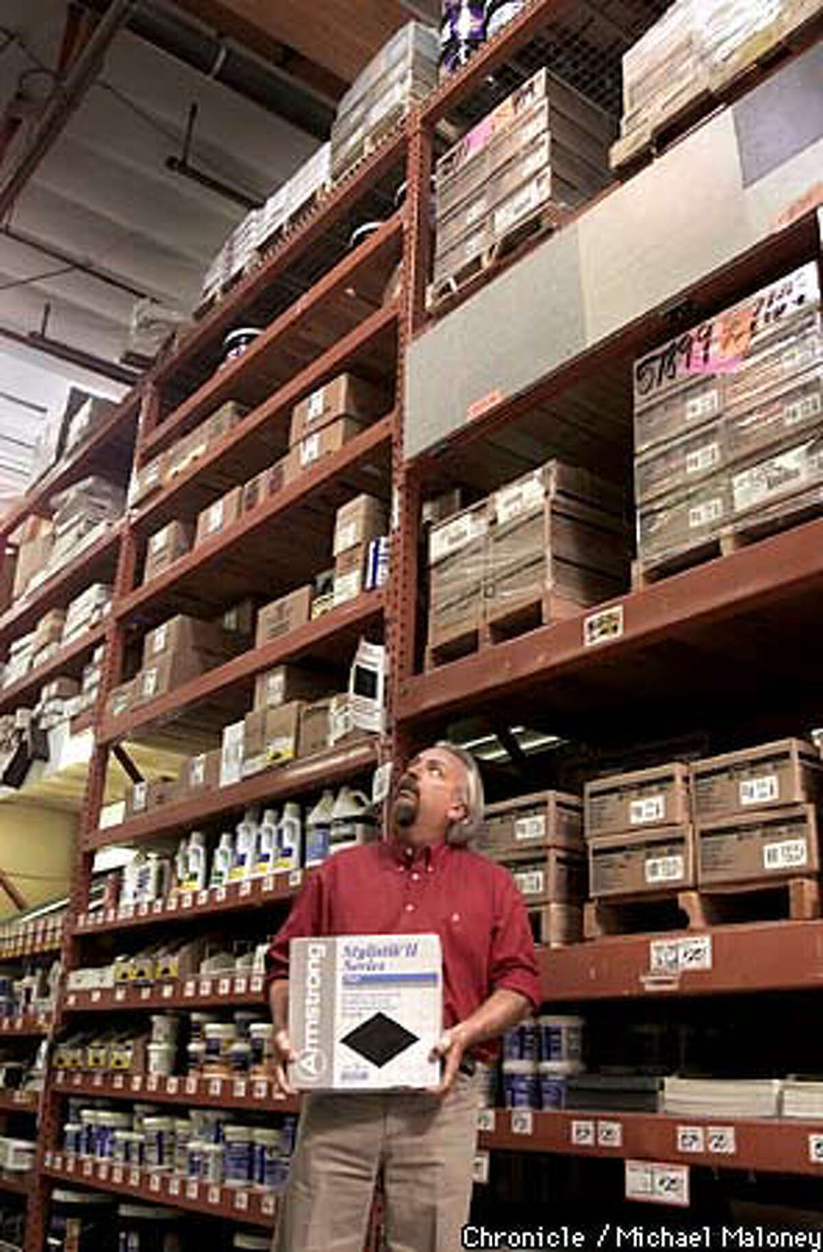 Dan Ernest held a 30-pound box of tiles similar to the one that hit him after it fell from the top shelf of the Home Depot store in Roseville. Chronicle photo by Michael Maloney