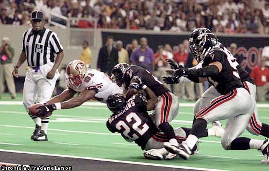 Terrell Owens (below), under siege by Gerald McBurrows (22) and other Falcons, stretched the ball over the goal line for a 6-yard touchdown catch. Chronicle photo by Frederic Larson / SAN FRANCISCO CHRONICLE