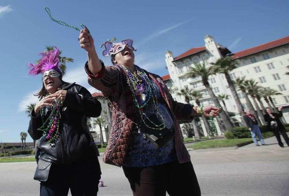 Lydia Draden laughs as Sharon Ash celebrates catching beads. Photo: Mayra Beltran, Houston Chronicle / © 2012 Houston Chronicle