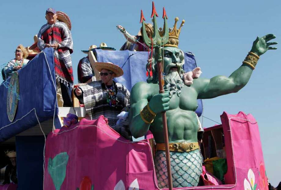 """Members of the Mystic Krewe of Aquarius rides the Krewe's float during the 25th Annual Mardi Gras Kick off Parade. Participating Krewes were """"Thalasar"""", Bacchus of Texas, Krewe DuLac and Krewe of Boudreaux. Photo: Mayra Beltran, Houston Chronicle / © 2012 Houston Chronicle"""