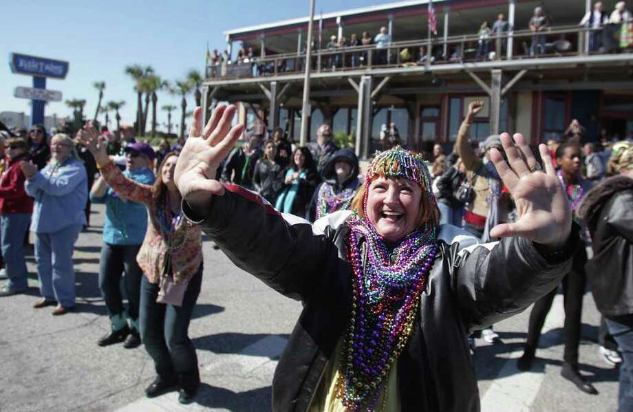 Rhonda Martin cheers with the crowd as they stands along the seawall during the Mystic Krewe of Aquarius 25th Annual Mardi Gras Kick off Parade. Photo: Mayra Beltran, Houston Chronicle / © 2012 Houston Chronicle