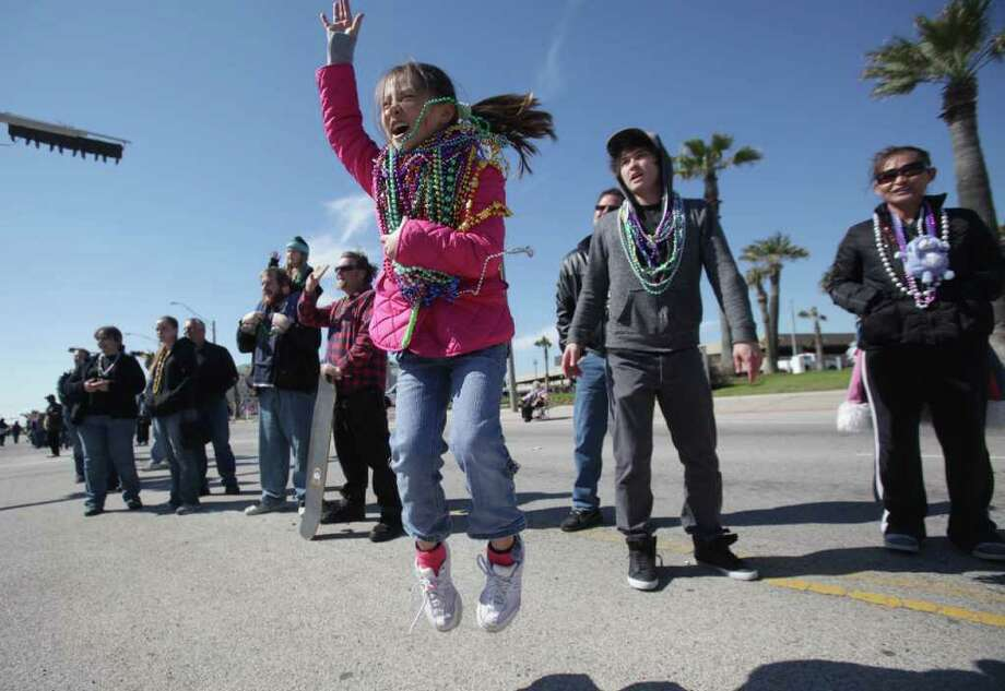 Jennifer Stine, 9, jumps for beads during the Mystic Krewe of Aquarius 25th Annual Mardi Gras Kick off Parade. Photo: Mayra Beltran, Houston Chronicle / © 2012 Houston Chronicle