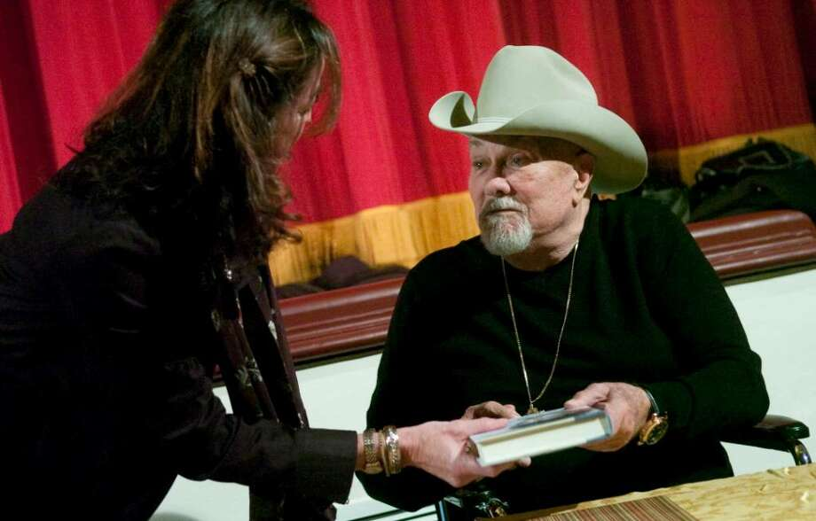 Tony Curtis hands an autographed copy of his book to Karen Eddowes, of Stamford, during a fundraising event at the Avon Theatre Film Center in Stamford, Conn. on Sunday, Nov. 11, 2009. Photo: Chris Preovolos / Stamford Advocate