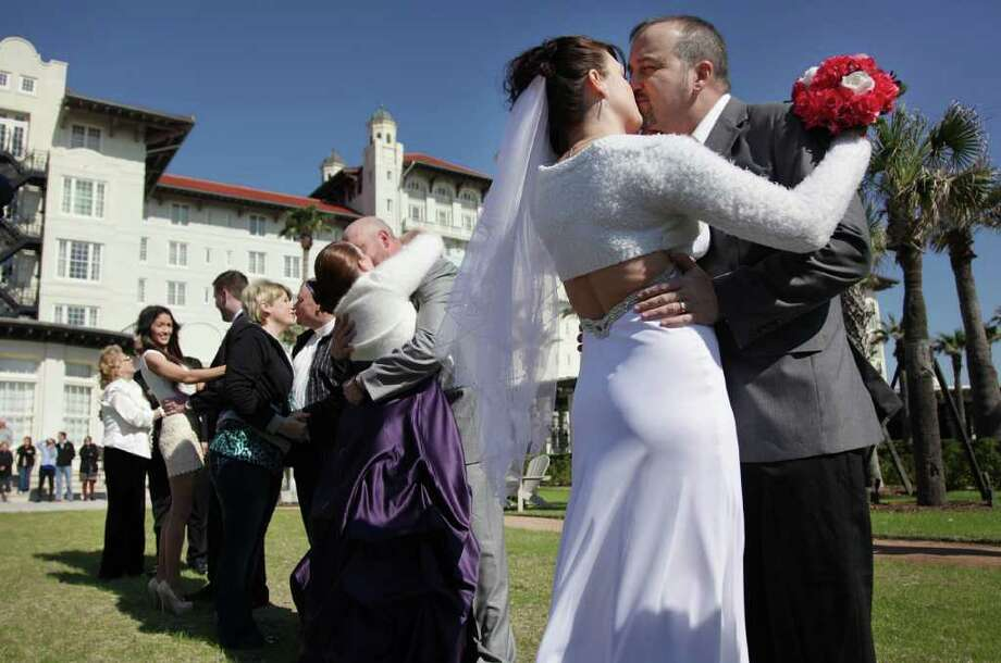 Robin Klimisch and Jason Klimisch kiss along with 16 other couples who were pronounced husband and wife during the Wedding Vow Renewal at Hotel Galvez & Spa on Saturday, Feb. 11, 2012, in Galveston. Photo: Mayra Beltran, Houston Chronicle / © 2012 Houston Chronicle
