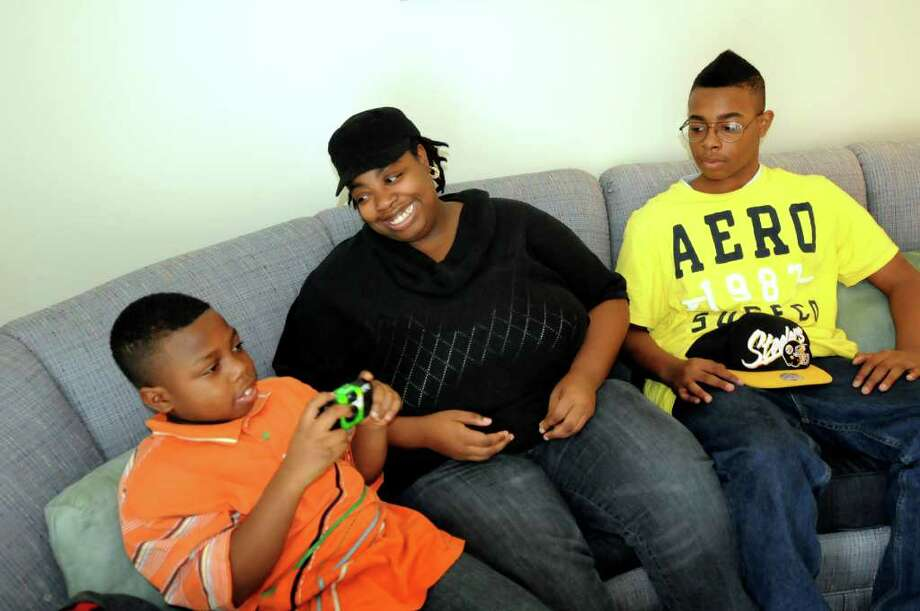 Angela Tingling, center, and her sons Nasim, 10, left, and Nazir, 12, relax on the couch after checking out their newly decorated Habitat for Humanity home on Saturday, Feb. 11, 2012, in Albany, N.Y. Sage College Interior Design students painted and decorated the home. (Cindy Schultz / Times Union) Photo: Cindy Schultz /  00016404A