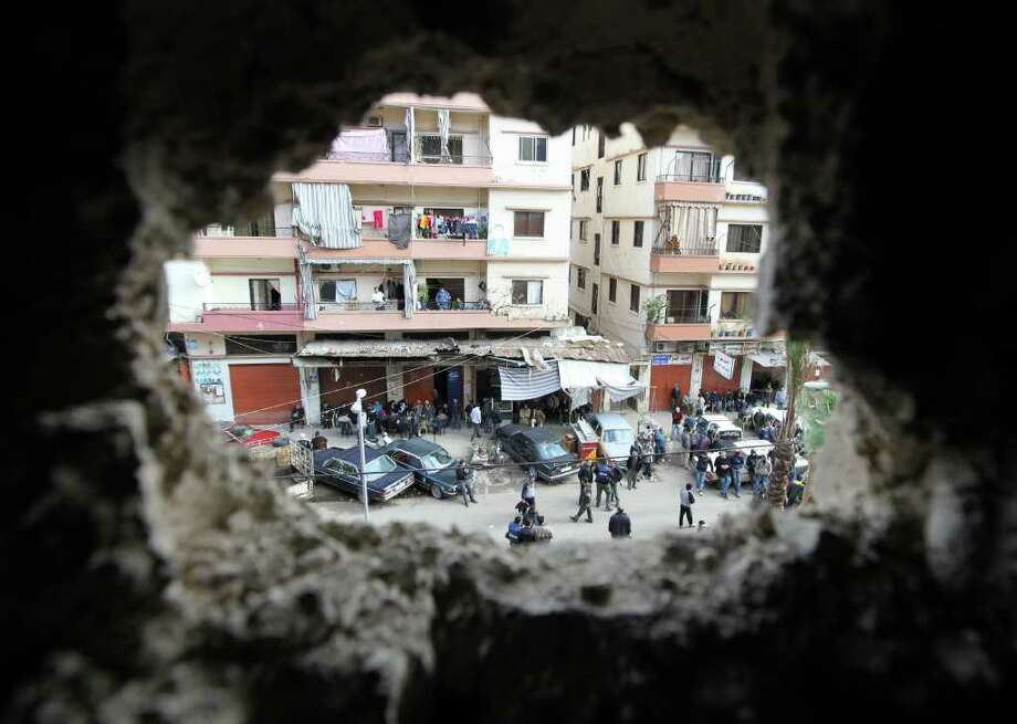 A hole in a wall caused by a rocket-propelled grenade offers a peek of a street in Tripoli, Lebanon, which borders Syria. Clashes between pro- and anti-Syria gunmen Saturday in the northern Lebanese city left two people dead. Photo: Bilal Hussein / AP