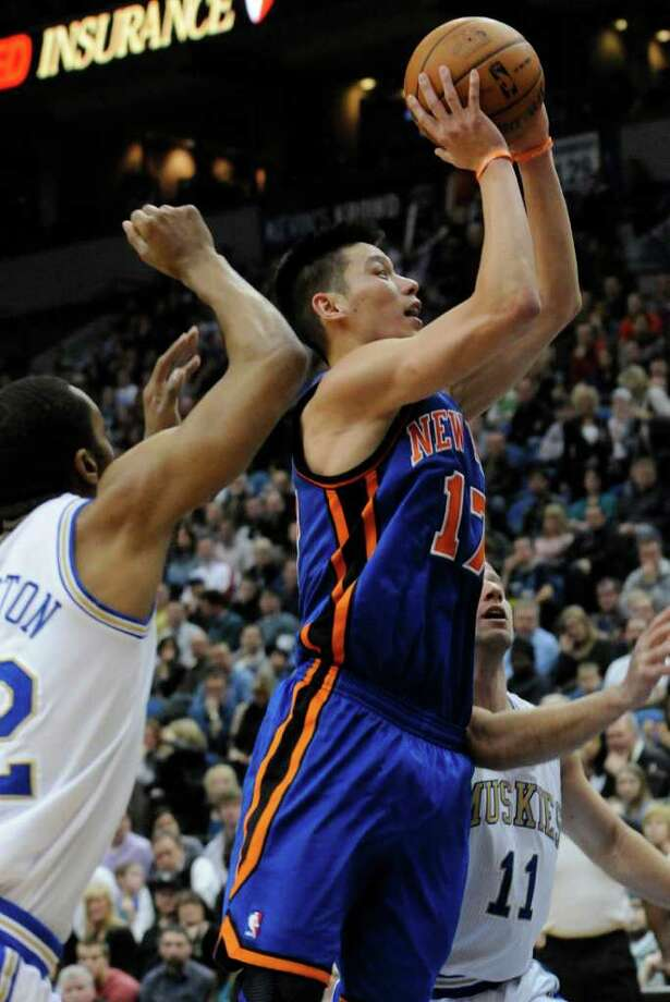 New York Knicks' Jeremy Lin, front right, lays up for two of his 20 game points on a shot in the second half of an NBA basketball game against the Minnesota Timberwolves, Saturday, Feb. 11, 2012, in Minneapolis.  Timberwolves' Wayne Ellington, left, and J.J. Berea, right, defend. The Knicks won 100-98. Photo: AP