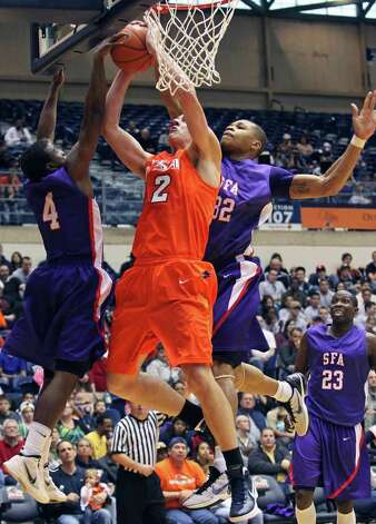 UTSA forward Jeromie Hill runs into a block at the hoop by Hal Bateman (4) and Jereal Scott as the  Roadrunners play the SFA Lumberjacks at the UTSA Convocation Center  on February 11, 2012 Tom Reel/ San Antonio Express-News Photo: TOM REEL, Express-News / San Antonio Express-News