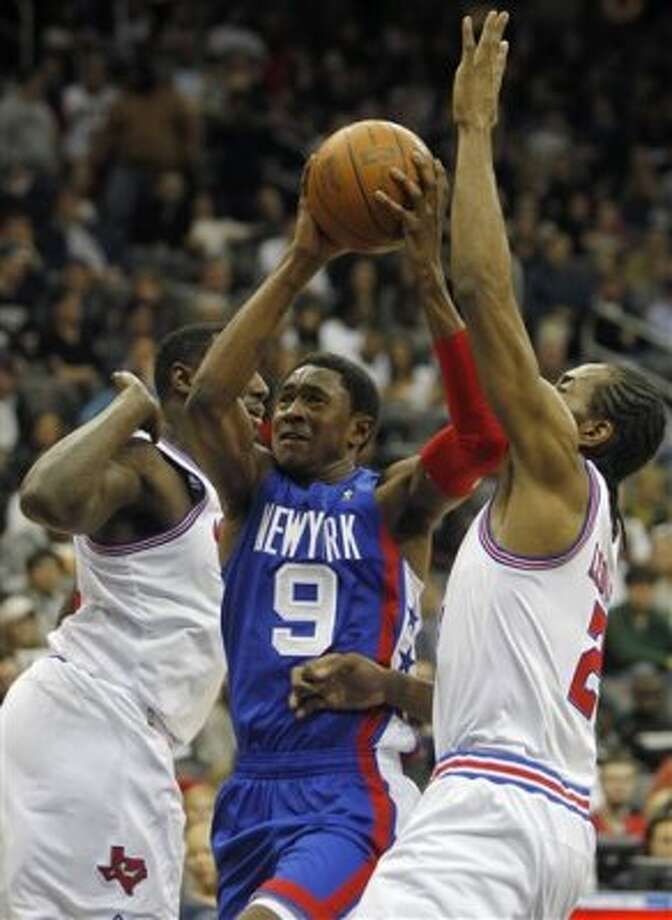 New Jersey Nets' MarShon Brooks (9) shoots between San Antonio Spurs' DeJuan Blair, left, and Kawhi Leonard (2) during an NBA basketball game in Newark, N.J., Saturday, Feb. 11, 2012. (AP Photo/Rich Schultz) (AP)