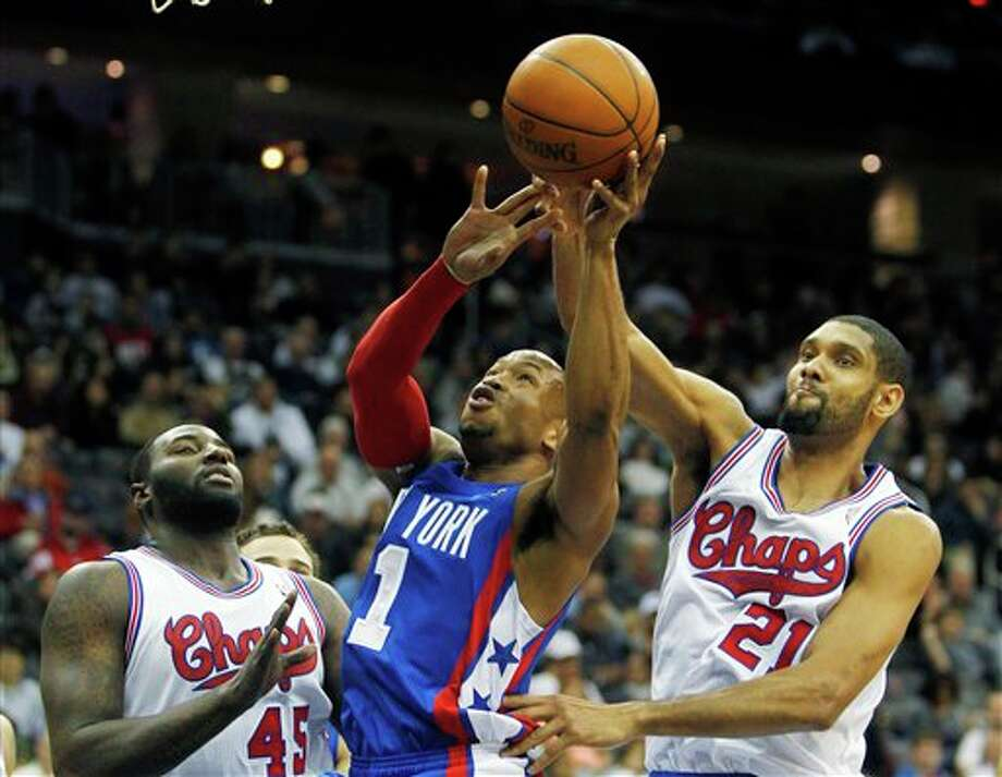 New Jersey Nets' Sundiata Gaines (1) loses control of the ball under pressure from San Antonio Spurs' Tim Duncan (21) and DeJuan Blair (45) during an NBA basketball game in Newark, N.J., Saturday, Feb. 11, 2012. The Spurs won 103-89. (AP Photo/Rich Schultz) (AP)