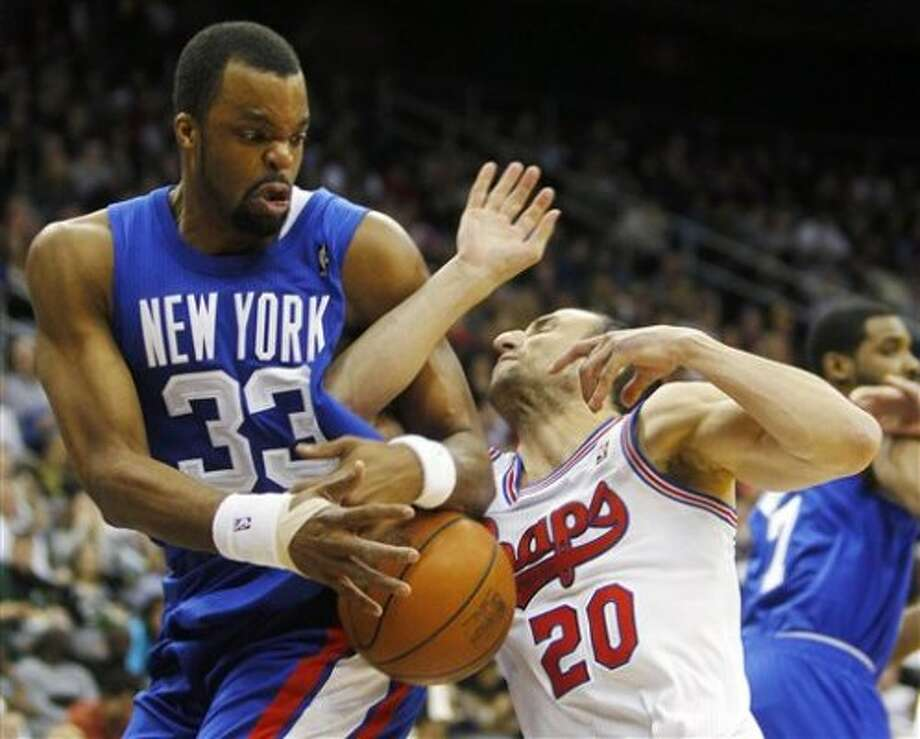 New Jersey Nets' Shelden Williams (33) fights for the ball with San Antonio Spurs' Manu Ginobili (20), of Argentina, in the second half during an NBA basketball game in Newark, N.J., Saturday, Feb. 11, 2012. The Spurs won 103-89. (AP Photo/Rich Schultz) (ASSOCIATED PRESS)