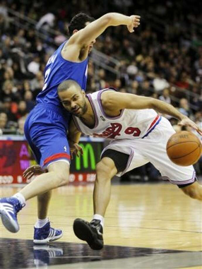 San Antonio Spurs' Tony Parker (9), of France, collides with New Jersey Nets' Jordan Farmar (2) as he drives to the basket in the second half during an NBA basketball game in Newark, N.J., Saturday, Feb. 11, 2012. The Spurs won 103-89. (AP Photo/Rich Schultz) (AP)