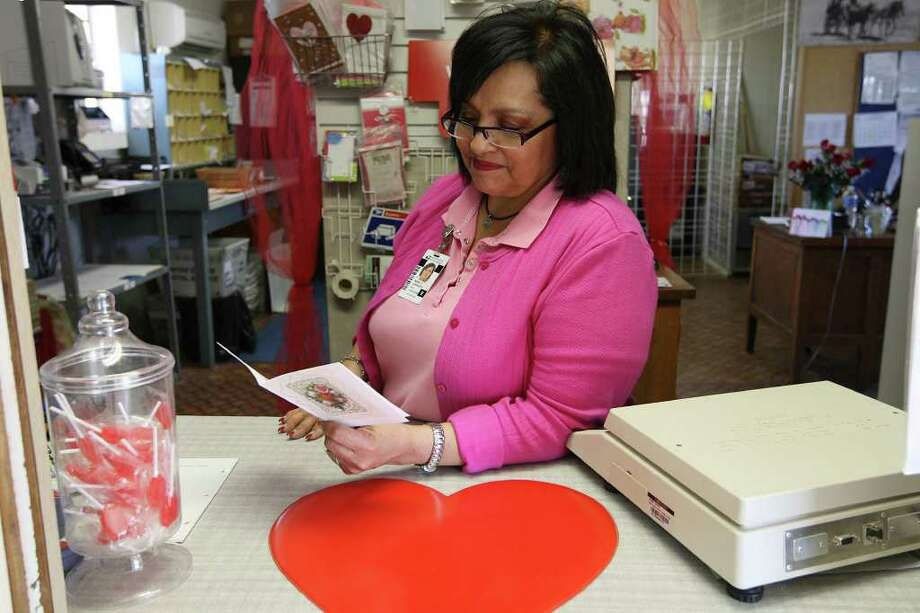 U.S. Postmaster Maria Carrasco reads a Thank You card sent to her at the Valentine, Texas post office, Tuesday, Feb. 7, 2012. The West Texas post office handles over 10 times more daily volume during the days leading up to Valentine's Day on February 14th. It's also on the list for possible closure by the U.S. Postal Service. Carrasco figured that she has hand-stamped Valentine cards destined for cities all over the world. Photo: Jerry Lara, San Antonio Express-News / © San Antonio Express-News
