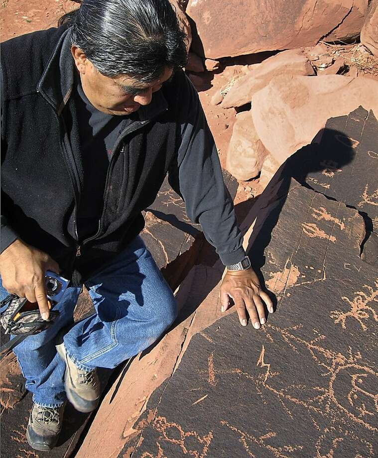 "ADVANCE FOR USE SUNDAY, JAN. 29, 2012 AND THEREAFTER - In this Nov. 29, 2011 photo, Lee Wayne Lomayestewa of the Hopi Cultural Preservation Office points to part of the ancient petroglyphs of Tutuveni near Tuba City, Ariz. The site, whose name means ""newspaper rock,"" contains some 5,000 petroglyphs of Hopi clan symbols, the largest known collection of such symbols in the American Southwest. (AP Photo/Pauline Arrillaga) Photo: Pauline Arrillaga, Associated Press"