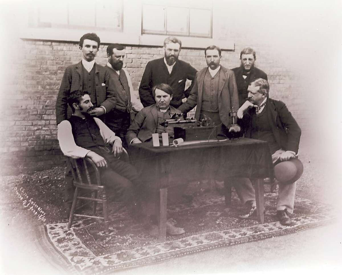 An undated handout image of Thomas Edison, seated center, Adelbert Theodor Edward Wangemann, standing behind him, and others at the Edison Laboratory. Tucked away for decades in a cabinet in Thomas Edison's laboratory, just behind the cot in which the great inventor napped, a trove of wax cylinder phonograph records has been brought back to life after more than a century of silence. (National Park Service via The New York Times) -- FOR EDITORIAL USE ONLY -
