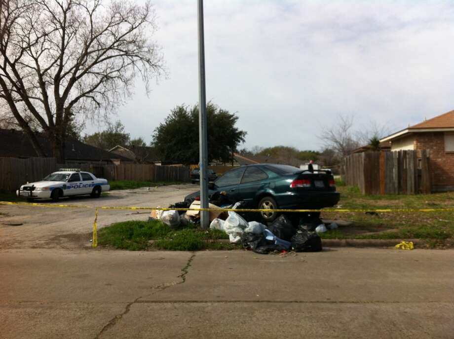 Houston police say this car was found in the yard of a home where a man's near-naked body was discovered.