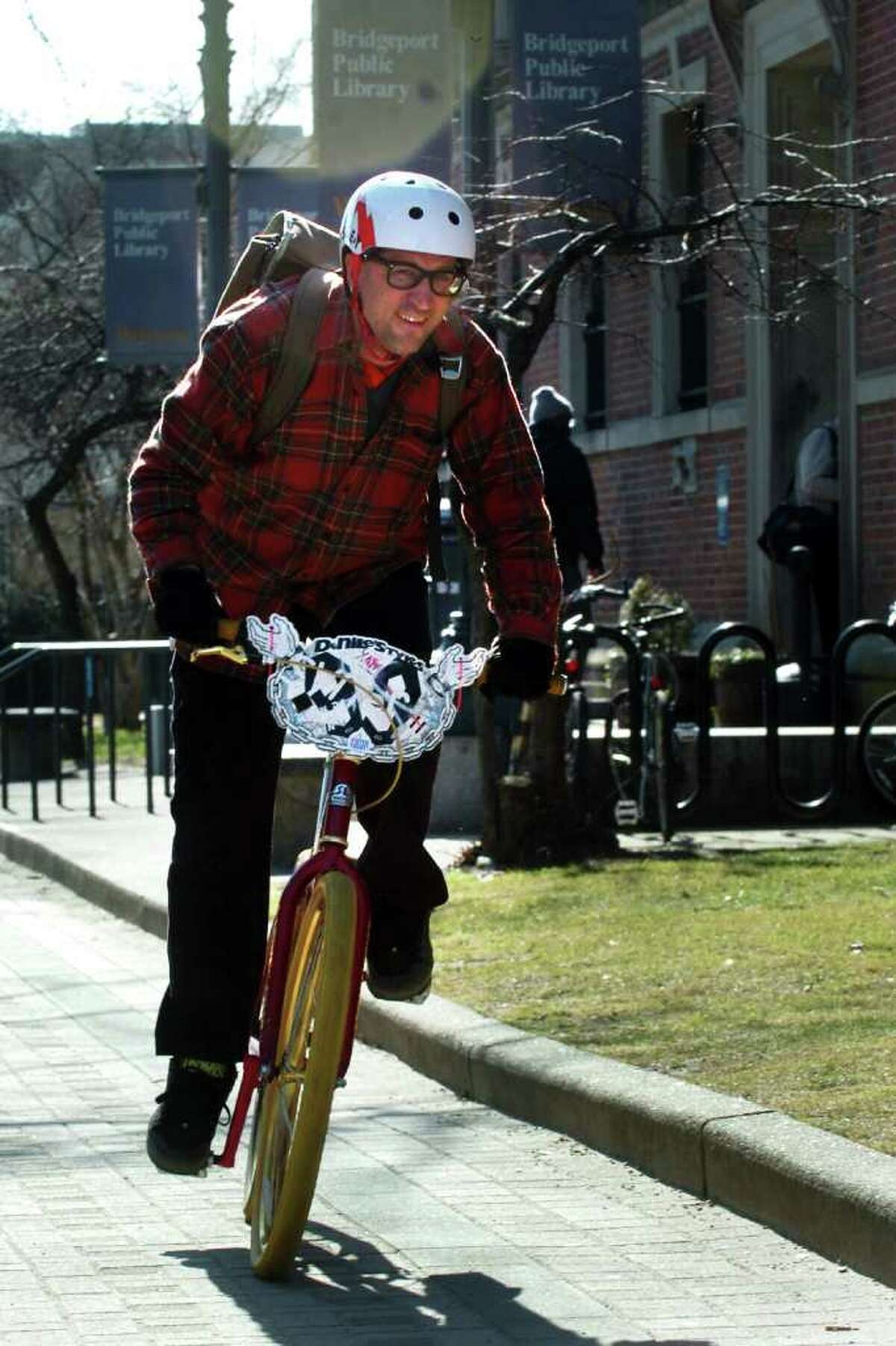 John Wilkins, of Bridgeport, rides his bicycle after returning books to the Burroughs & Saden Library in downtown Bridgeport, Conn. Feb. 10th, 2012.