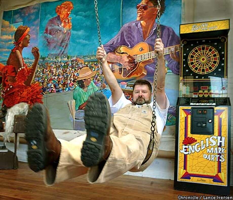 A Swinging time: Dan Fontes made his studio home into an arcade of amuse-ments, both artistic and historical. Behind him, is a bar game and his 1987 Festival of the Arts mural. Chronicle photo by Lance Iversen