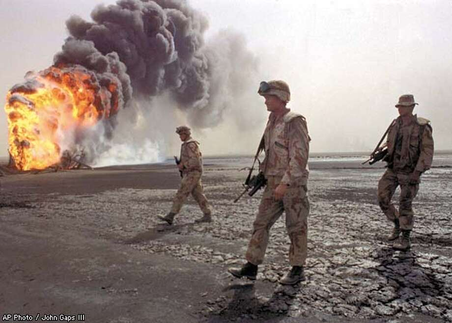 A U.S. Marine patrol walks across the charred oil landscape near a burning well during perimeter security patrol near Kuwait City on March 7, 1991. AP Photo / John Gaps III Photo: JOHN GAPS III