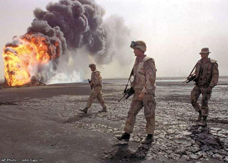 A U.S. Marine patrol walks across the charred oil landscape near a burning well during perimeter security patrol near Kuwait City on March 7, 1991. AP Photo / John Gaps III Photo: JOHN GAPS III