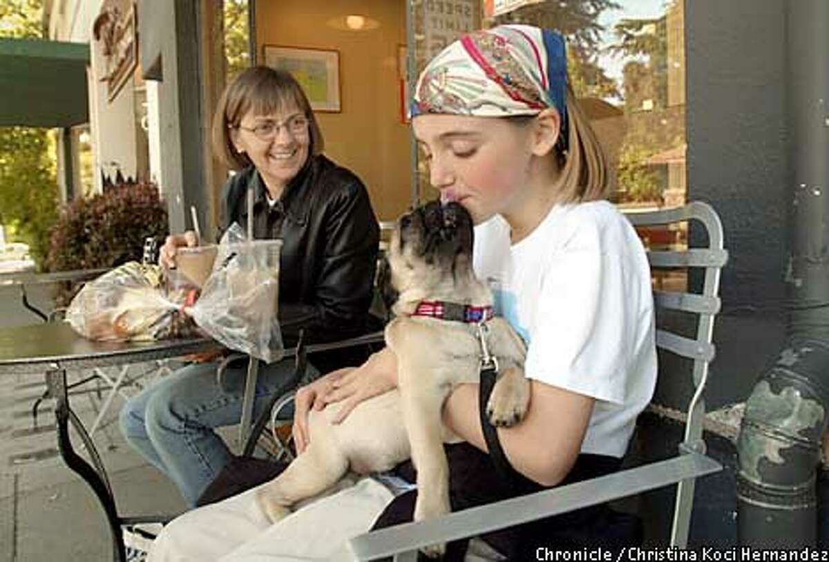 CHRISTINA KOCI HERNANDEZ/CHRONICLE Katy Buder,11, gets a kiss from her dog, George, in front of Semifreddi's Bakery, on Claremont Ave., in Berkeley. With her is her mom, Barbara Buder.The Claremont neighborhood in Berkeley.