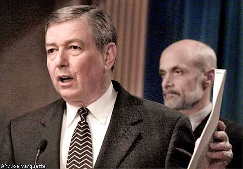 Attorney General John Ashcroft, left, holds the indictments against John Walker Lindh during a news conference at the Justice Department in Washington Tuesday, Jan. 15, 2002. Ashcroft announced the Bush administration will charge Lindh with conspiracy to kill U.S. nationals in Afghanistan. Assistant Attorney General Michael Chertoff looks on at right. (AP Photo/Joe Marquette) Photo: JOE MARQUETTE