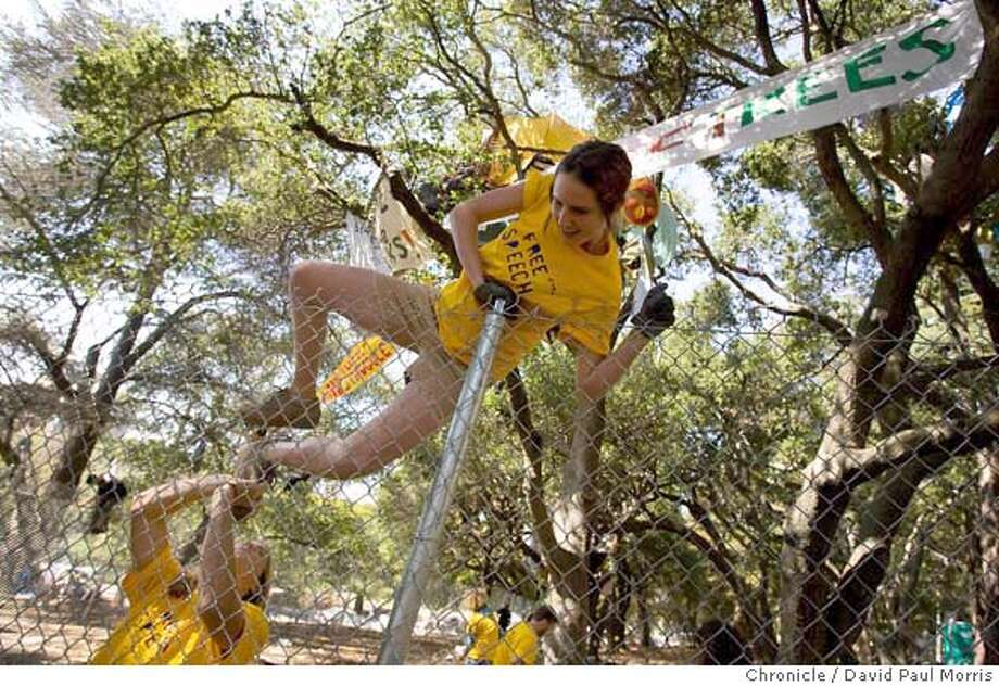 BERKELEY, CA - SEPTEMBER 14: Supporters of the tree sitting protesters jump over a fence surrounding a grove of oak trees and tree sitters at UC Berkeley September 14, 2007 in Berkeley, California. They jumped over the fence to bring food and water to the protesters in the trees as well as to clean up inside the fenced in area. (Photo by David Paul Morris/The Chronicle) Photo: David Paul Morris