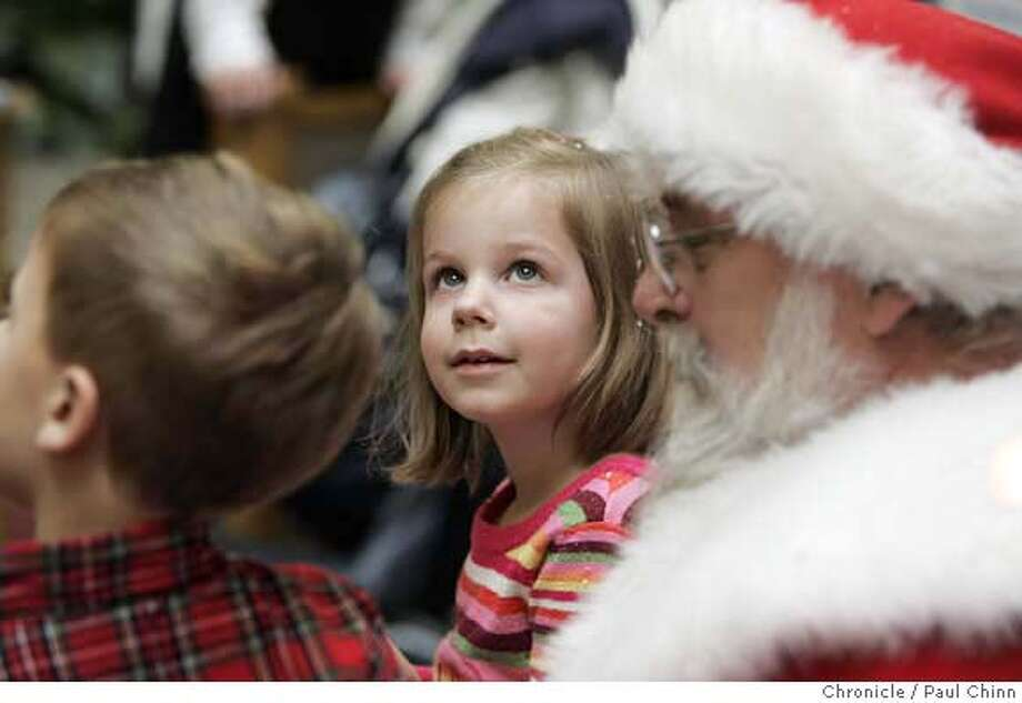 Madeline Franz, 5, visiting Santa with her brother Jacob, 4, is mesmerized by the snow and penguins at Santa's display. Shoppers waiting to visit Santa Claus walk through a snow globe at Sunvalley Mall in Concord, Calif. on Friday, Dec. 1, 2006. PAUL CHINN/The Chronicle  **Madeline Franz, Jacob MANDATORY CREDIT FOR PHOTOGRAPHER AND S.F. CHRONICLE/ - MAGS OUT Photo: PAUL CHINN