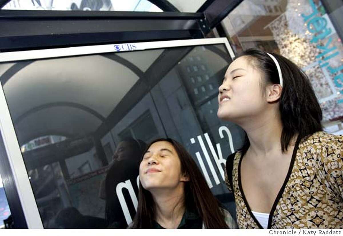 COOKIES05_063_RAD.jpg SHOWN: L to R: Kirsten Jung, age 14, a student at Sacred Heart, and Stephanie Jung, age 19, a student at the Fashion institute of Design and Marketing, both of San Francisco, made a special trip to this bus shelter after hearing about it, to smell the scent. Both said it did indeed smell like cookies, and yes, it made them want milk. Story is about the reaction to the chocolate smell wafting from Muni bus shelters with the
