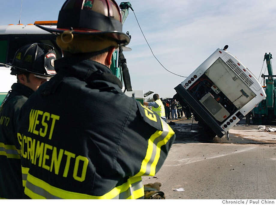 Firefighters stand watch as a tow truck crew uprights a bus that crashed on Highway 50 at Jefferson Boulevard in West Sacramento, Calif. on Thursday, Nov. 30, 2006. More than 20 occupants were slightly injured when the bus overturned while shuttling students and faculty from the UC Davis campus to the university's medical center in Sacramento. Eastbound lanes were closed for several hours.  PAUL CHINN/The Chronicle Photo: PAUL CHINN