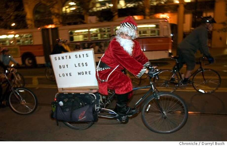 """mass_002_db.JPG  A bicycle rider calling himself """"anti-capitalist Santa,"""" rides while participating in """"critical mass,"""" ride down Market Street slowing traffic in San Francisco, CA, on Friday, November, 24, 2006. 11/24/06  Darryl Bush / The Chronicle ** (cq) Ran on: 11-25-2006  A bicyclist calling himself &quo;anti-capitalist Santa&quo; sends a message to post-Thanksgiving shoppers Friday as he rides down Market Street as part of Critical Mass, a monthly event that promotes cycling. Photo: Darryl Bush"""