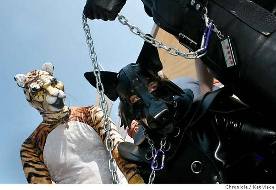 """""""Growl"""" aka Edwin Aoki from Mt. View stops to admire """"Smash the Leather Wolf"""" aka Bryan Maternach from Boulder Creek who is led on a chain by Robert Green (hand only)from Los Angeles at the annual Folsom Street Festival on Sunsday September 24, 2006. Kat Wade/The Chronicle ** (subjects) cq Photo: Kat Wade"""