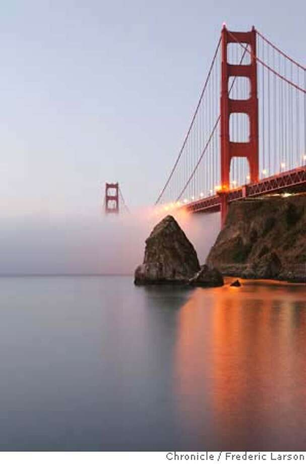 The September low hugging fog slowly makes its way under the Golden Gate Bridge seen at Fort Baker during sunrise. 9/12/06  {Frederic Larson/ The Chronicle} MANDATORY CREDIT FOR AND SAN FRANCISCO CHRONICLE/ -MAGS OUT Photo: Frederic Larson