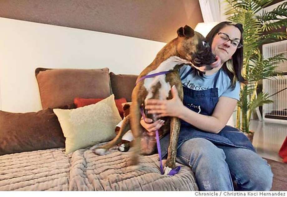 "Employee, Vanessa Slater, with dog, ""Athena,"" after a massage. WAG dog hotel in West Sacramento. Next month, Wag, a high-end �dog hotel� will open its flagship palace in San Francisco�s South of Market district, making it the largest kennel in this dog-crazed town. Each of the 240 �suites� at Wag will come fitted with heated floors, color televisions sets, and a Web cam so owners can log on and take a peek at their napping Fido. The weird part: The swanky digs for dogs, once considered an extravagance for the wealthy and mildly insane, is becoming the norm in the rapidly growing $4 billion-a-year kennel industry. [(CHRISTINA KOCI HERNANDEZ/THE CHRONICLE) Mandatory Credit For Photographer and San Francisco Chronicle/No-Sales-Mags Out Photo: Christina Koci Hernandez"