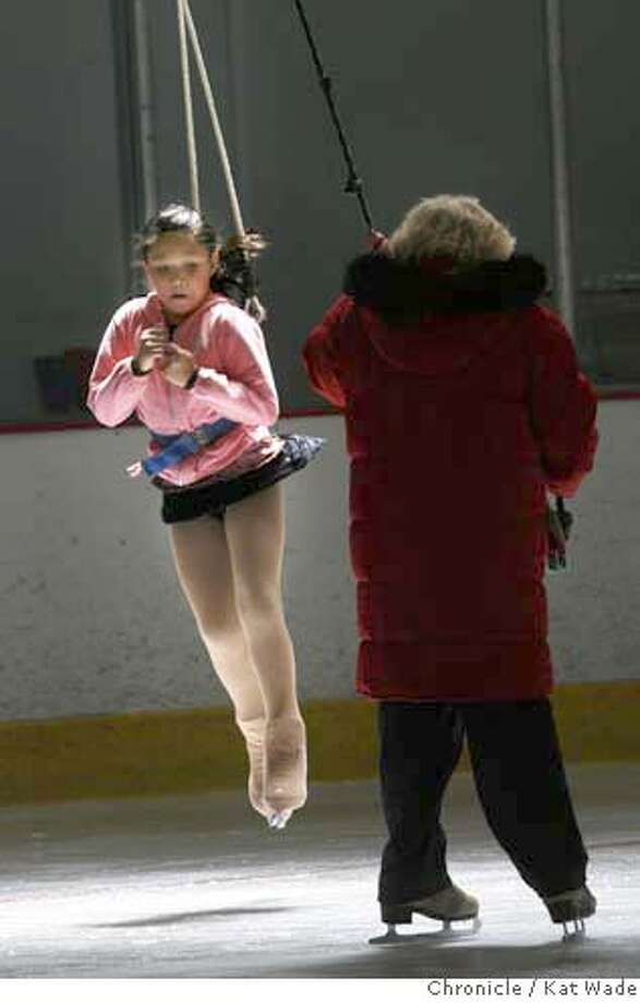 WADEice_004_KW_.jpg STAND ALONE: (L to R) Tiffany Tran, 9, from Danville uses a harness to practice jumps and spins on ice under the supervision of her coach Jeanette Nelson at the Dublin Iceland Ice Skating rink Wednesday afternoon July 19, 2006. Tran is preparing for the 26th annual St. Moritz Ice Skating Competition begining with preliminaries on September 6th at Oakland Ice Center. Kat Wade/The Chronicle ** Tiffany Tran, 9, (subject) and Jeanette Nelson (Subject)cq Mandatory Credit for San Francisco Chronicle and photographer, Kat Wade, Mags out Photo: Kat Wade