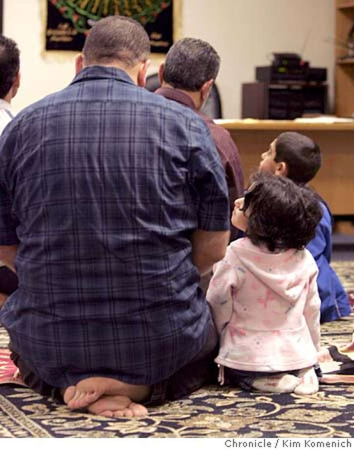 IRAQ17_087_KK.JPG  Sajed Aal-abdulrasul and daughter Israa Aal-abdulrasul, 2 1/2, during evening prayers at the Iraq Community Center in Sunnyvale.  We visit the Iraq Community Center in Sunnyvale to illustrate a story Vanessa Hua about Iraqis across the Bay Area who just last year participated in the Iraqi national elections with great optimism They look toward the third anniversary of the Iraq war's beginning with decided pessimism. With the possibility of civil war looming ever larger, and with domestic life increasingly disrupted, they offer a variety of prognoses for their country.  San Francisco Chronicle photo by Kim Komenich  3/16/06 � Copyright 2006 Kim Komenich/San Francisco Chronicle Photo: Kim Komenich