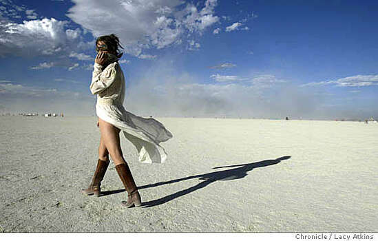 Angela Sanders of Michigan covers her face from the sand as she dances in Black Rock at Burning Man 2004,  Photo: LACY ATKINS