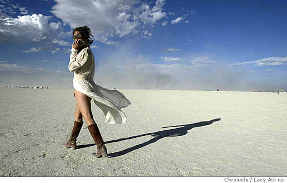 Angela Sanders of Michigan covers her face from the sand as she dances in Black Rock, Wed. Sept.1, at Burning Man. People continue to gather at Black Rock desert for the 18th annual Burning Man celebration,Wed. Sept.1, 2004, .  LACY ATKINS/ The Chronicle Photo: LACY ATKINS