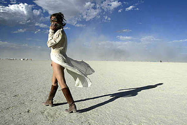 Angela Sanders of Michigan covers her face from the sand as she dances in Black Rock, Wed. Sept.1, at Burning Man. People continue to gather at Black Rock desert for the 18th annual Burning Man celebration,Wed. Sept.1, 2004, .  LACY ATKINS/ The Chronicle