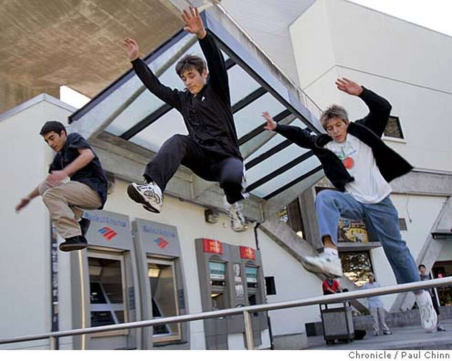 Pierre Blosse, Andrey Pfening and Alex Jacks (L to R) leap over a railing during a parkour jam at SF State in San Francisco, Calif. on 3/18/06. Parkour is a relatively new trend where participants leap over railings, jump from the top of staircases and other bizarre stunts.  PAUL CHINN/The Chronicle MANDATORY CREDIT FOR PHOTOG AND S.F. CHRONICLE/ - MAGS OUT Photo: PAUL CHINN