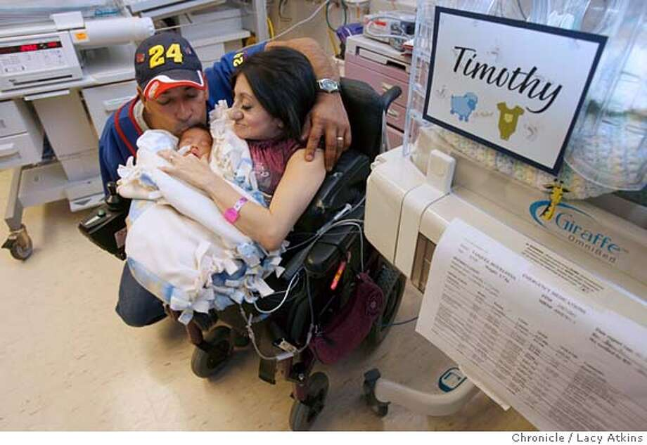 Roy Vasquez gives his new son Timothy Abraham a kiss as he lies in his mother's, Eloysa arms at the Lucile Packard Children's Hospital, Feb. 9, 2006, in Stanford. and Roy Vasquez with their newborn Timothy Abraham at the Lucile Packard Children's Hospital, Feb. 9, 2006, in Stanford. Timothy was born Jan. 24, 2006 at the weight of 3 pounds, 11 ounces, with the help the folks at Lucile Packard Children's Hospital. Photographer:Atkins, Lacy MANDATORY CREDIT FOR PHOTOG AND SF CHRONICLE/ -MAGS OUT Photo: LACY ATKINS