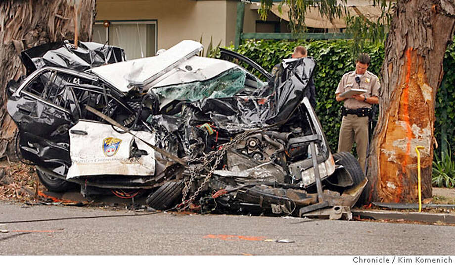 The crushed remains of a Burlingame police car is investigated by a California Highway Patrol officer (pictured). He is among several CHP officers involved in the investigation of a collision between the car and a school bus Friday afternoon on El Camino Real between Palm and Edgehill.  Kim Komenich / The Chronicle Photo: Kim Komenich
