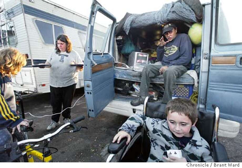 FAMILY. Dinner at the Silver's van takes on a special tone as Tom's beloved Red Sox are playing the Oakland A's...here Kim serves dinner around the television which is running off a neighbor's generator. BRANT WARD / The Chronicle Photo: BRANT WARD