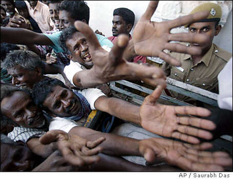 People plead for rice from an aid distributing truck in Nagappattinam, India, Tuesday, Jan. 4, 2005. Hundreds of thousands of people have lost their homes as the Dec. 26 tsunami in southern Asia and eastern Africa killed about 150,000 people. (AP Photo/Saurabh Das Photo: SAURABH DAS