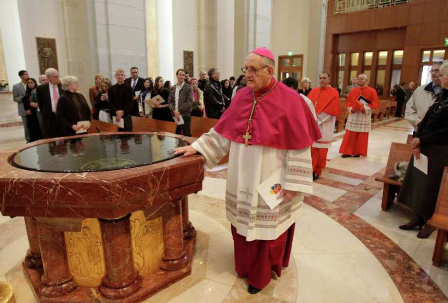 Most Reverend Joseph A. Fiorenza, the Archbishop Emeritus of Galveston-Houston, touches holy water as he enters during procession for the Mass of Institution for the Ordinariate of the Chair of Saint Peter at the Co-Cathedral of the Sacred Heart, 1111 St. Joseph Parkway, Sunday, Feb. 12, 2012, in Houston.  During the mass the Reverend Jeffrey Steenson was installed as the first Ordinary, or head, of the Ordinariate of the Chair of Saint Peter and given the title of Monsignor. Photo: Melissa Phillip, Houston Chronicle / © 2011 Houston Chronicle