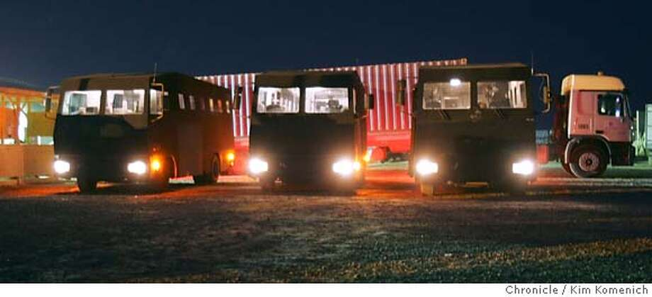 "Three ""rhinos"" await passengers at Camp Stryker. The armored truck behind the rhinos carries passengers' bags and cargo from the airport to the International Zone.  Soldiers and civilian contractors board the ""Rhino"", a heavily armored Winnebago-looking bus and begin a heavily guarded convoy from Camp Stryker at the Baghdad Airport to the International Zone in downtown Baghdad. The three Rhinos were escorted by two helicopters and several Bradley fighting vehicles. San Francisco Chronicle Photo by Kim Komenich  9/23/05 Photo: Kim Komenich"