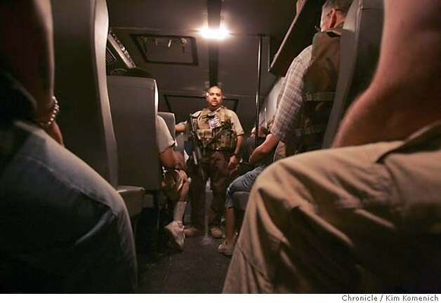 "At Camp Stryker,Special Agent Ricardo Gibert (cq) of the Diplomatic Security Services of the U.S. Department of State briefs rhino passengers on attack scenarios before the convoy departs for the International Zone in Baghdad  Soldiers and civilian contractors board the ""Rhino"", a heavily armored Winnebago-looking bus and begin a heavily guarded convoy from Camp Stryker at the Baghdad Airport to the International Zone in downtown Baghdad. The three Rhinos were escorted by two helicopters and several Bradley fighting vehicles. San Francisco Chronicle Photo by Kim Komenich  9/23/05 Photo: Kim Komenich"