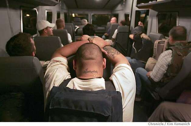 "Jose Calzoncinth (cq) of Houston, Texas, a Kellog, Brown and Root contract worker, rests before the rhino departs. The tattoo on his neck says ""Katherina""- he had it done in honor of his eight year-old daughter Katherina.  Soldiers and civilian contractors board the ""Rhino"", a heavily armored Winnebago-looking bus and begin a heavily guarded convoy from Camp Stryker at the Baghdad Airport to the International Zone in downtown Baghdad. The three Rhinos were escorted by two helicopters and several Bradley fighting vehicles. San Francisco Chronicle Photo by Kim Komenich  9/23/05 Photo: Kim Komenich"